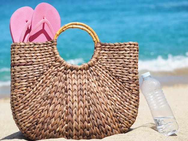 Saco de vime natural marrom com chinelos na praia ao lado de uma garrafa de água plástica