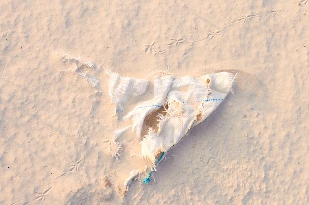 Saco descartado enterrado na areia