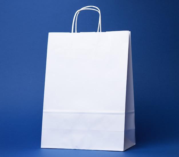 Saco descartável de papel branco com alças em fundo azul, close-up