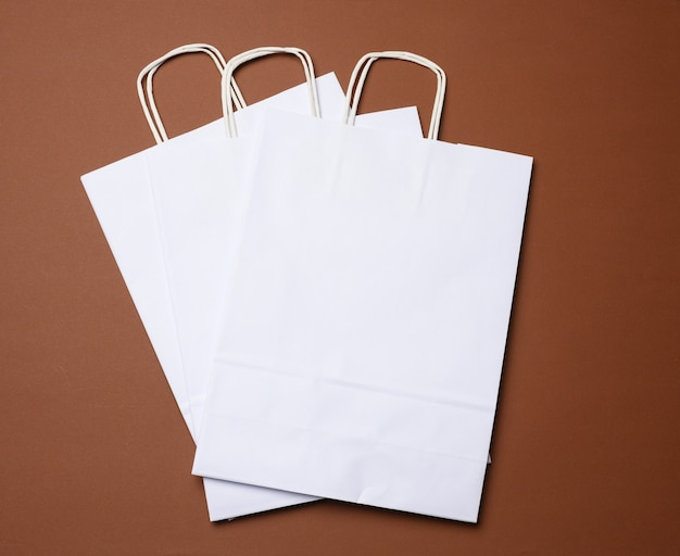 Saco descartável de papel branco com alças em fundo marrom, close-up