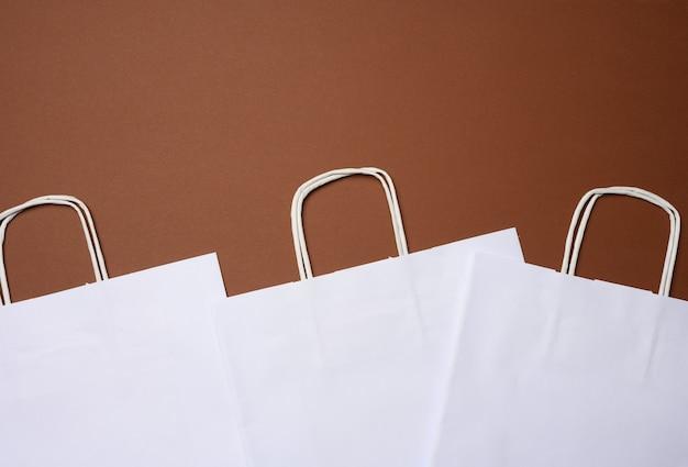 Saco descartável de papel branco com alças em fundo marrom, vista superior