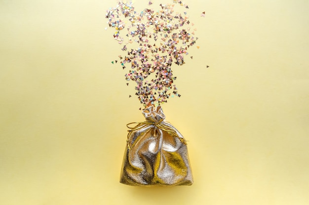 Saco do presente da tela dourada em um fundo amarelo. doces multicoloridos.
