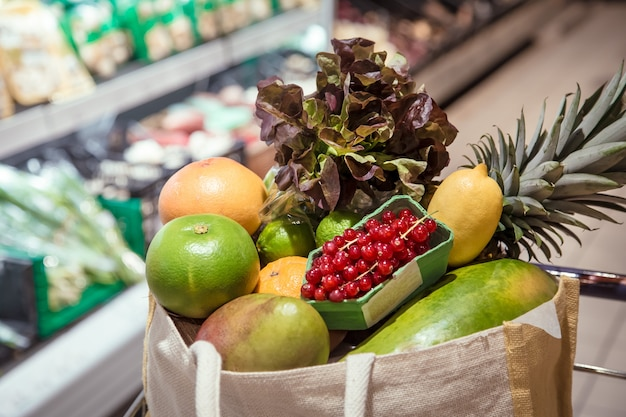 Saco ecológico com diferentes frutas e vegetais. comprando no supermercado