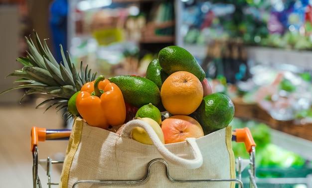 Saco ecológico com diferentes frutas e vegetais. compras no supermercado.