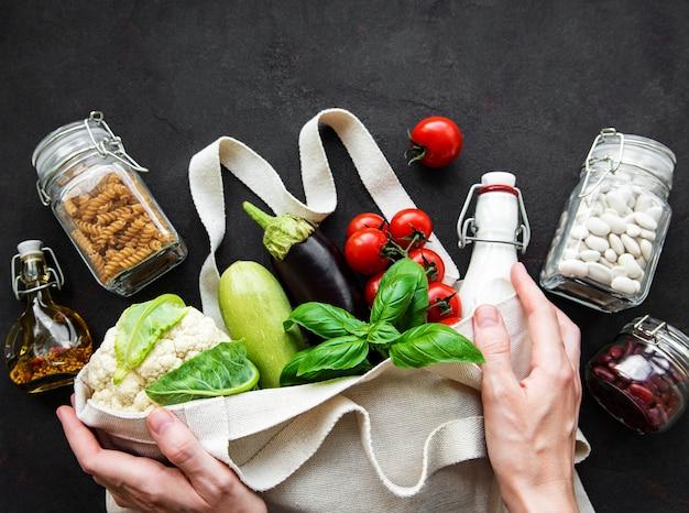 Saco ecológico com frutas e vegetais, potes de vidro com feijão e macarrão