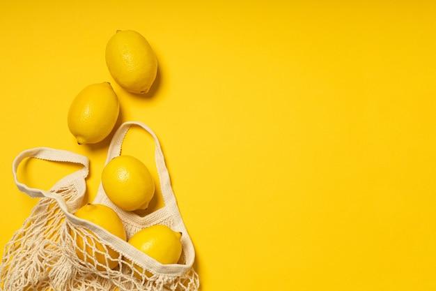 Saco ecológico com limões amarelos maduros em fundo amarelo