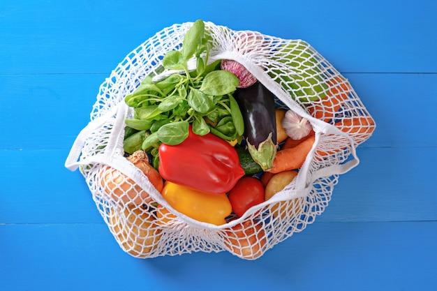 Saco ecológico com vegetais em fundo azul, compras online de alimentos, doações, mercado online