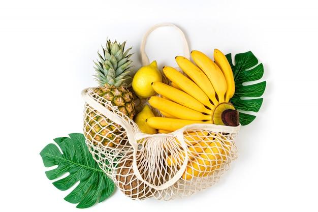 Saco ecológico de algodão comercial com frutas orgânicas banana, frutas cítricas, coco e abacaxi no fundo branco