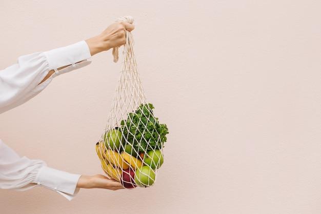 Saco ecológico reutilizável para fazer compras. saco de compras de cordão com frutas nas mãos de uma jovem