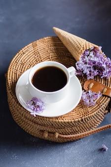 Saco elegante do rattan, xícara de café e lilás roxo no cone do waffle no fundo concreto azul.