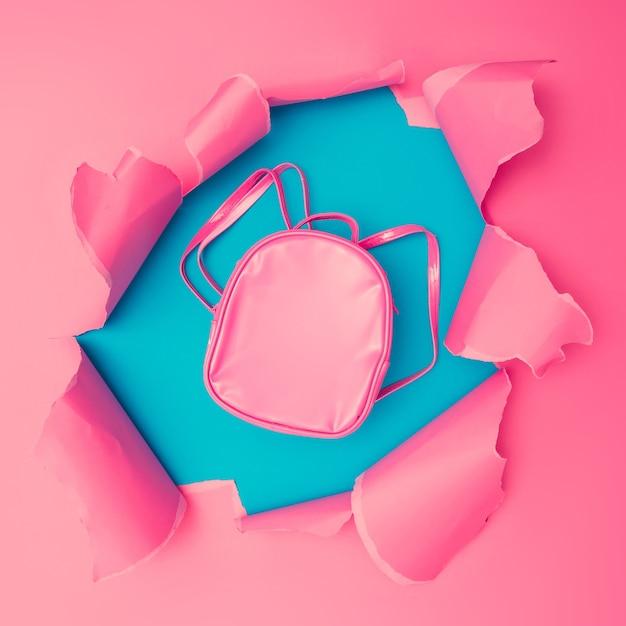 Saco escolar com papel rasgado rosa vivo. fundo do buraco de estouro. conceito de papel de parede colorido abstrato mínimo.