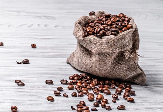 Saco feito de pano de estopa com grãos de café e alguns grãos próximos a ele.