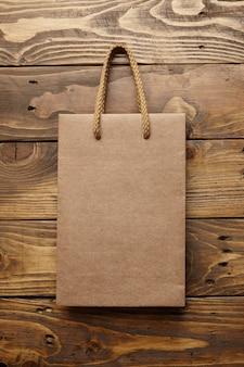 Saco marrom para viagem de papel reciclado artesanal em mesa de madeira rústica