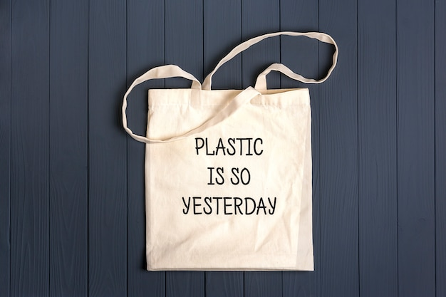 Saco não - tecido eco - friendly em uma mesa de madeira cinza escuro o plástico é ontem