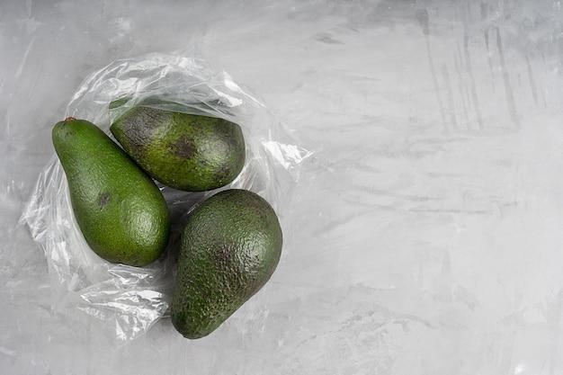 Saco plástico cheio de abacate verde maduro sobre concreto cinza