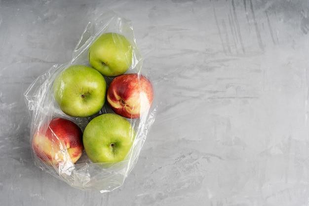 Saco plástico cheio de maçãs maduras e nectarinas no concreto