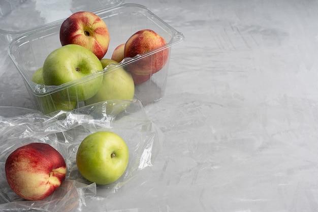Saco plástico e recipiente cheio de maçãs maduras e nectarinas no concreto