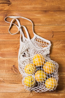 Saco reciclável com laranjas em fundo de madeira