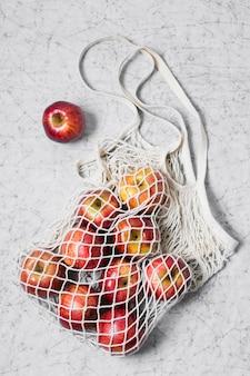 Saco reciclável com maçãs vermelhas