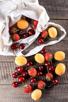 Saco reutilizável com damasco, morango e cereja no fundo da mesa de madeira. vista do topo. zero conceito de resíduos