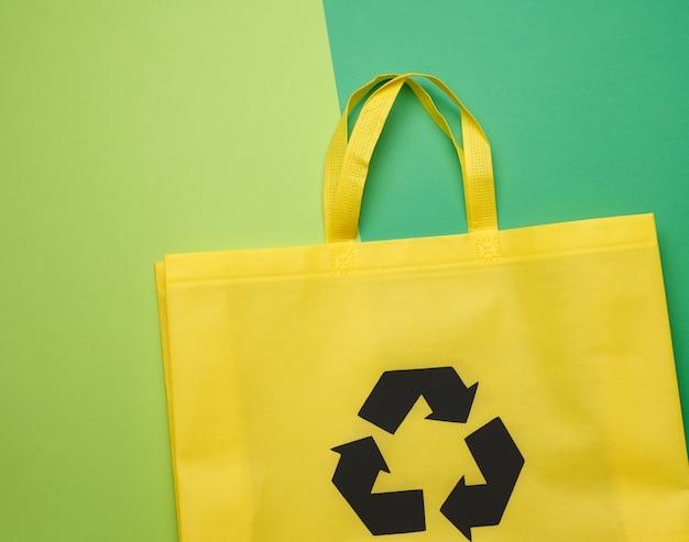 Saco têxtil amarelo reutilizável feito de viscose em um fundo verde
