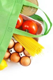 Saco verde cheio de comida saudável em um fundo branco