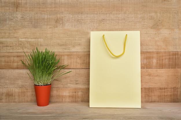Sacola amarela em uma mesa de madeira. planta de casa verde. consumidor