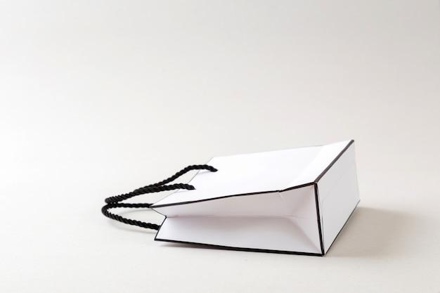 Sacola de compras branca, um fundo branco e espaço para texto ou texto sem formatação