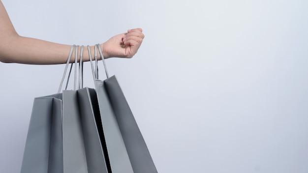 Sacola de compras cinza segura pelo braço de mulher asiática de negócios e fundo branco