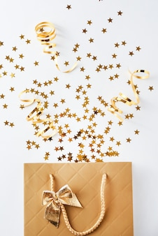 Sacola de compras com confetes festivos em fundo branco