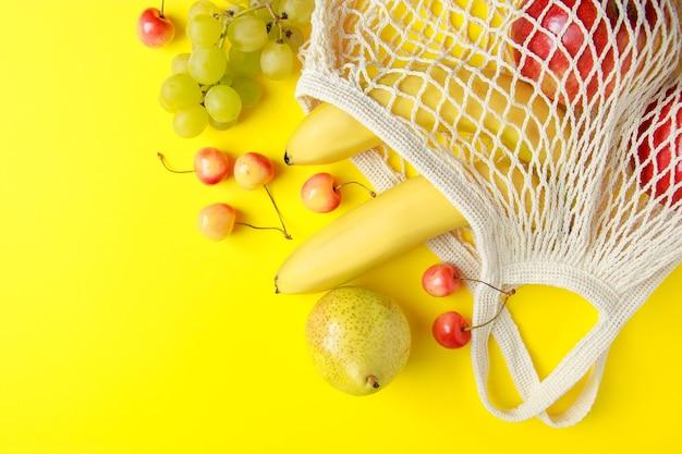 Sacola de compras de algodão ecologicamente correta frutas maduras em uma sacola de malha em fundo amarelo comida vegana orgânica
