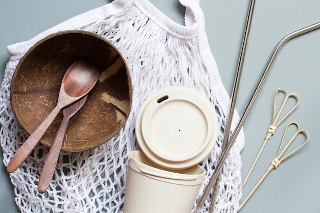 Sacola de compras de algodão, xícara de bambu, canudos de metal, talheres de coco de madeira e tigela na vista superior da mesa cinza. estilo de vida sustentável e conceito de desperdício zero