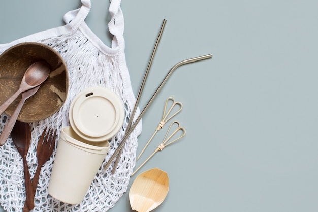 Sacola de compras de algodão, xícara de bambu, canudos de metal, talheres de coco de madeira e tigela na vista superior do plano de fundo cinza. estilo de vida sustentável e conceito de desperdício zero