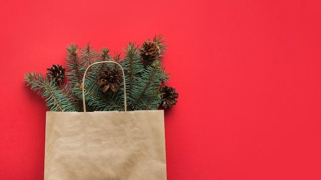 Sacola de compras de natal com cone natural e galhos de pinheiro no espaço vermelho