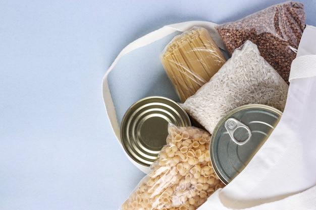 Sacola de compras de têxteis com suprimentos de comida na superfície azul clara. arroz, trigo sarraceno, macarrão, comida enlatada. entrega de comida, doação, espaço para texto