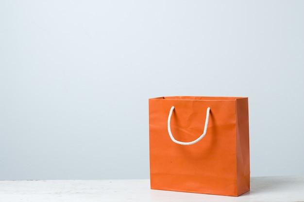 Sacola de compras laranja na mesa de madeira