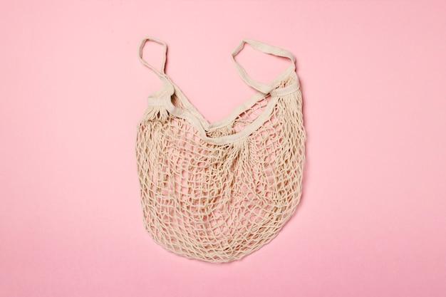 Sacola de compras na moda em uma superfície rosa. conceito de compras, venda, viagem de compras. vista plana, vista superior