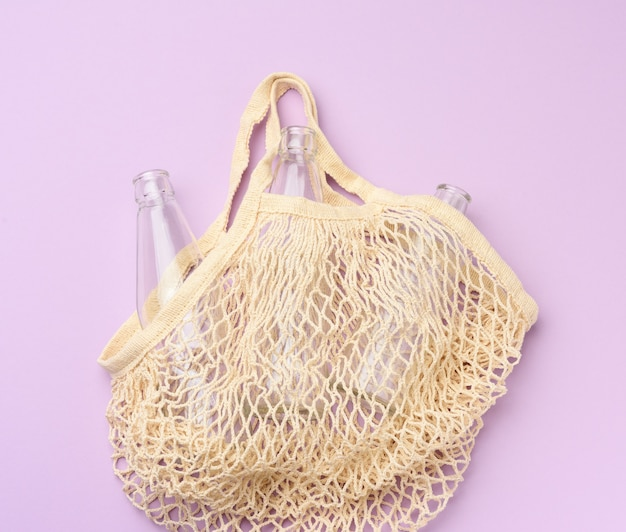 Sacola de compras reutilizável de têxteis com garrafas vazias em um fundo roxo, desperdício zero
