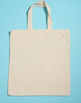 Sacola de lona bege amigável de eco de linho vazia para a marca no fundo azul. saco transparente reutilizável para mantimentos, mock up. postura plana