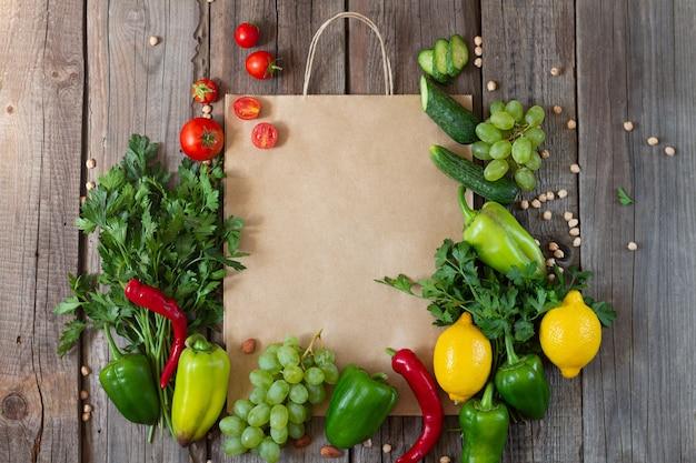 Sacola de papel com vegetais frescos e frutas na mesa de madeira