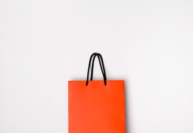 Sacola de papel laranja com alças pretas na mesa branca