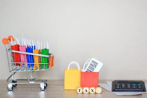 Sacola de papel no carrinho de modelo em miniatura com calculadora na mesa, compras e aumento de impostos