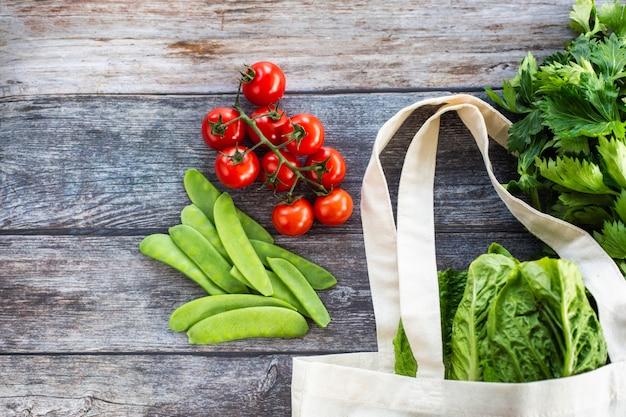 Sacola ecológica com legumes orgânicos frescos e salada em fundo de madeira, flat lay