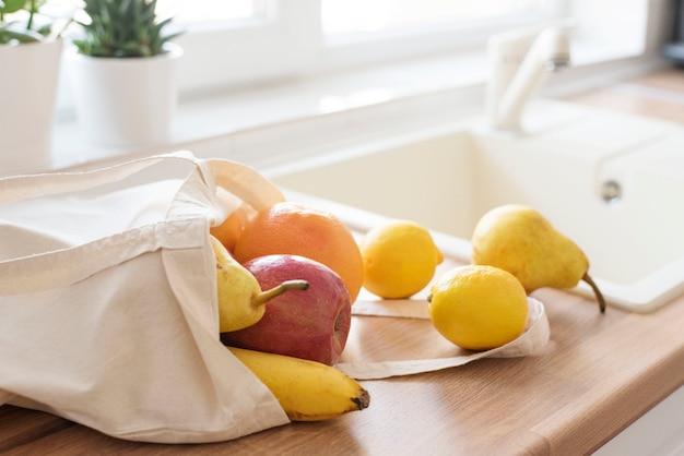Sacola têxtil cheia de frutas frescas no balcão da cozinha