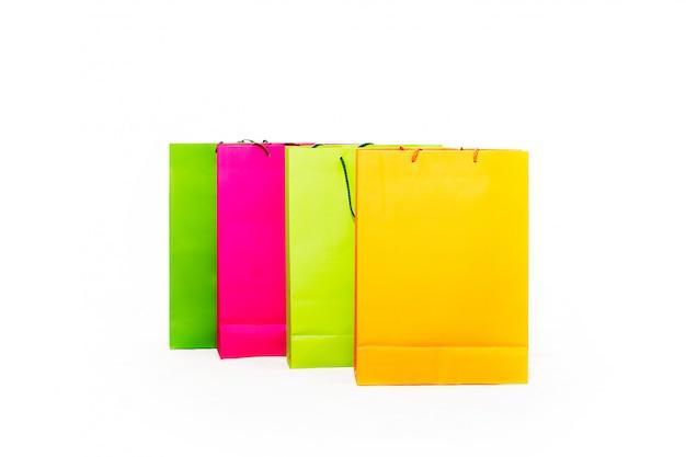 Sacolas coloridas sortidas, incluindo amarelo, laranja, rosa e verde sobre fundo branco