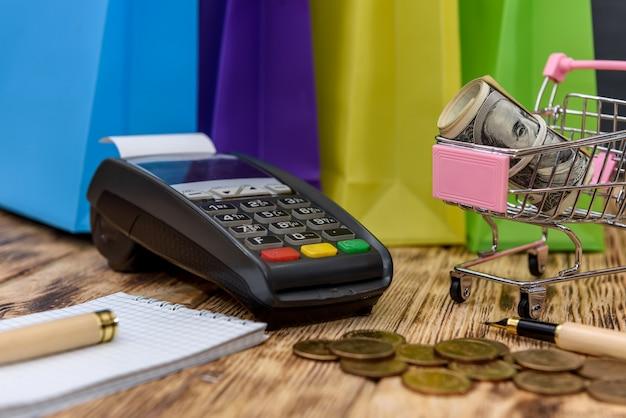 Sacolas de compras coloridas com terminais e notas de dólar
