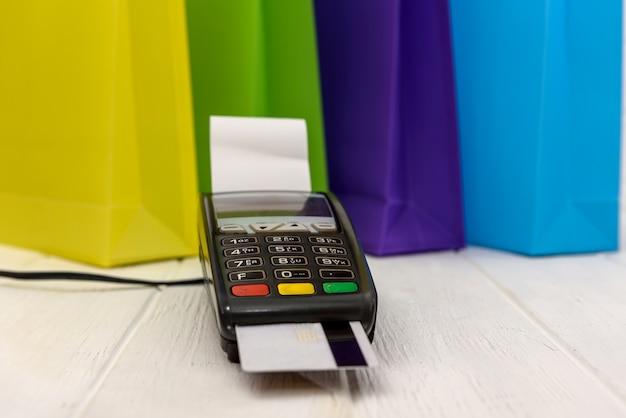 Sacolas de compras coloridas com terminal e cartão de crédito