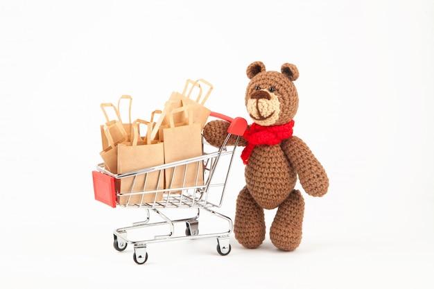 Sacolas de compras. comércio de vendas, descontos. uso de materiais ecológicos. desperdício zero. branco, isolado. urso de pelúcia de malha, amigurumi, feito à mão