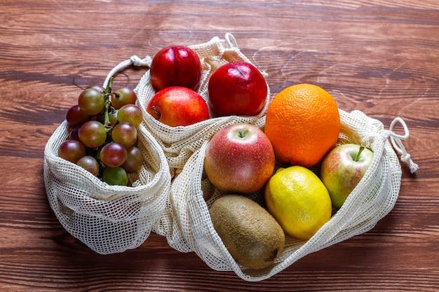 Sacolas de compras de algodão bege simples e ecológicas para comprar frutas e verduras com frutas de verão.