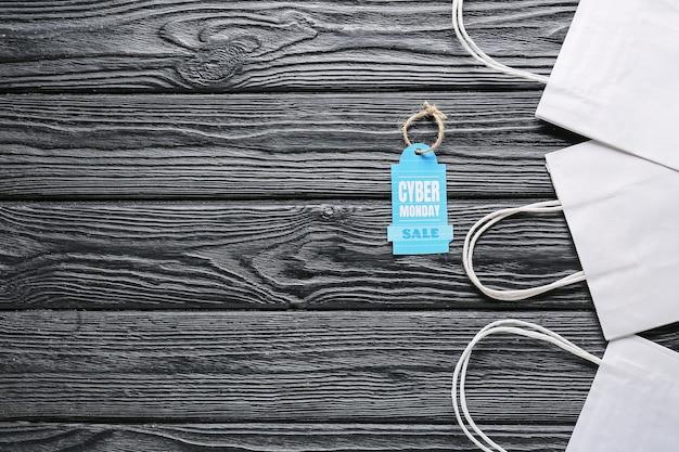 Sacolas de compras e etiqueta com o texto venda de segunda-feira cyber em superfície de madeira escura